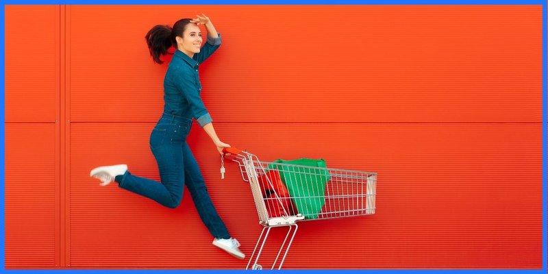 Einkaufswagen und Frau, die Luftsprünge macht